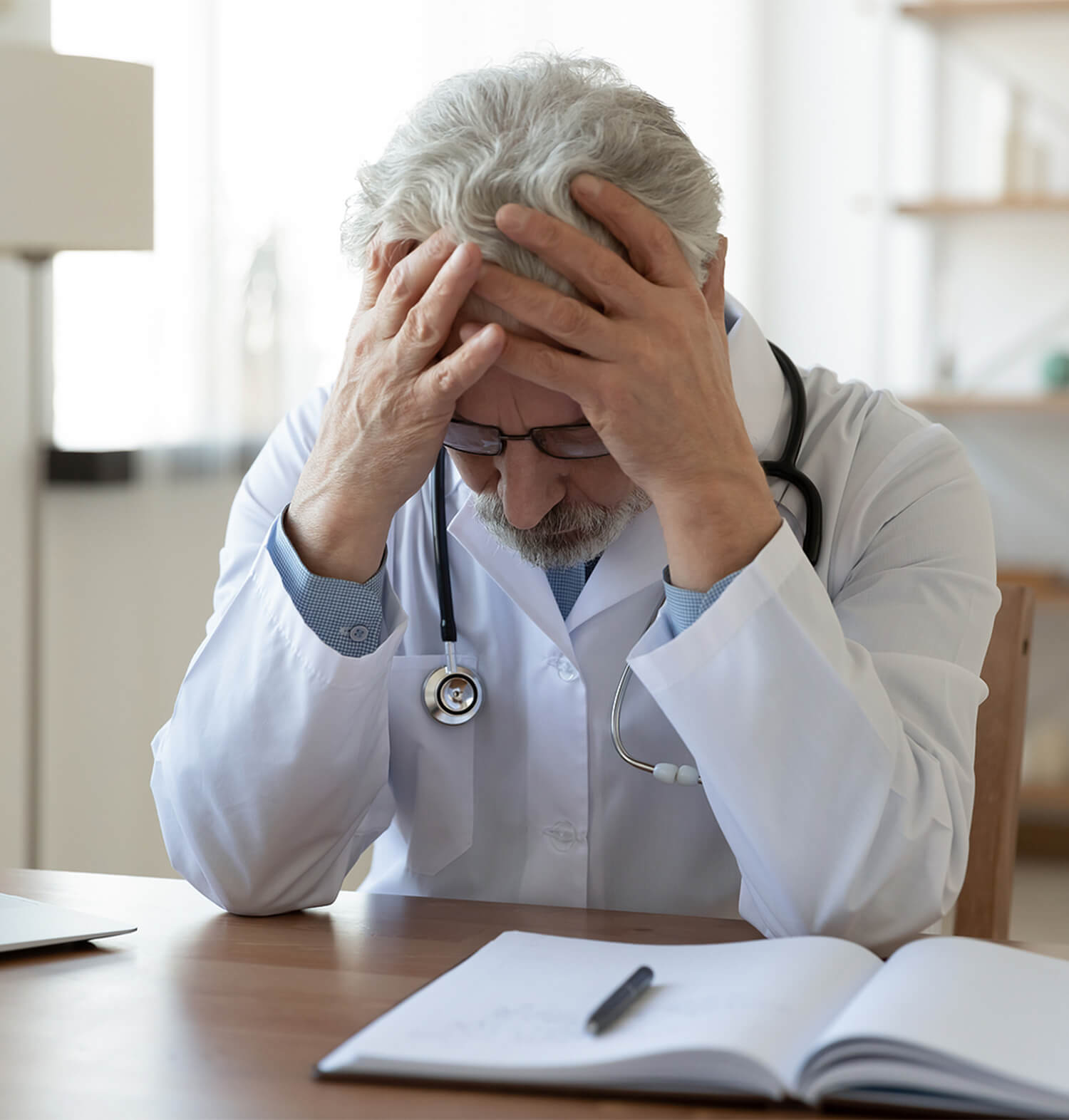 Doctor sitting at desk with notes open holding head in hand distressed. Regardless of who you are, symptoms of anxiety can affect you. When it starts to interfere, this means talking with a psychotherapist can help. Get psychotherapy support in anxiety treatment in Torrance, CA and surrounding areas soon!