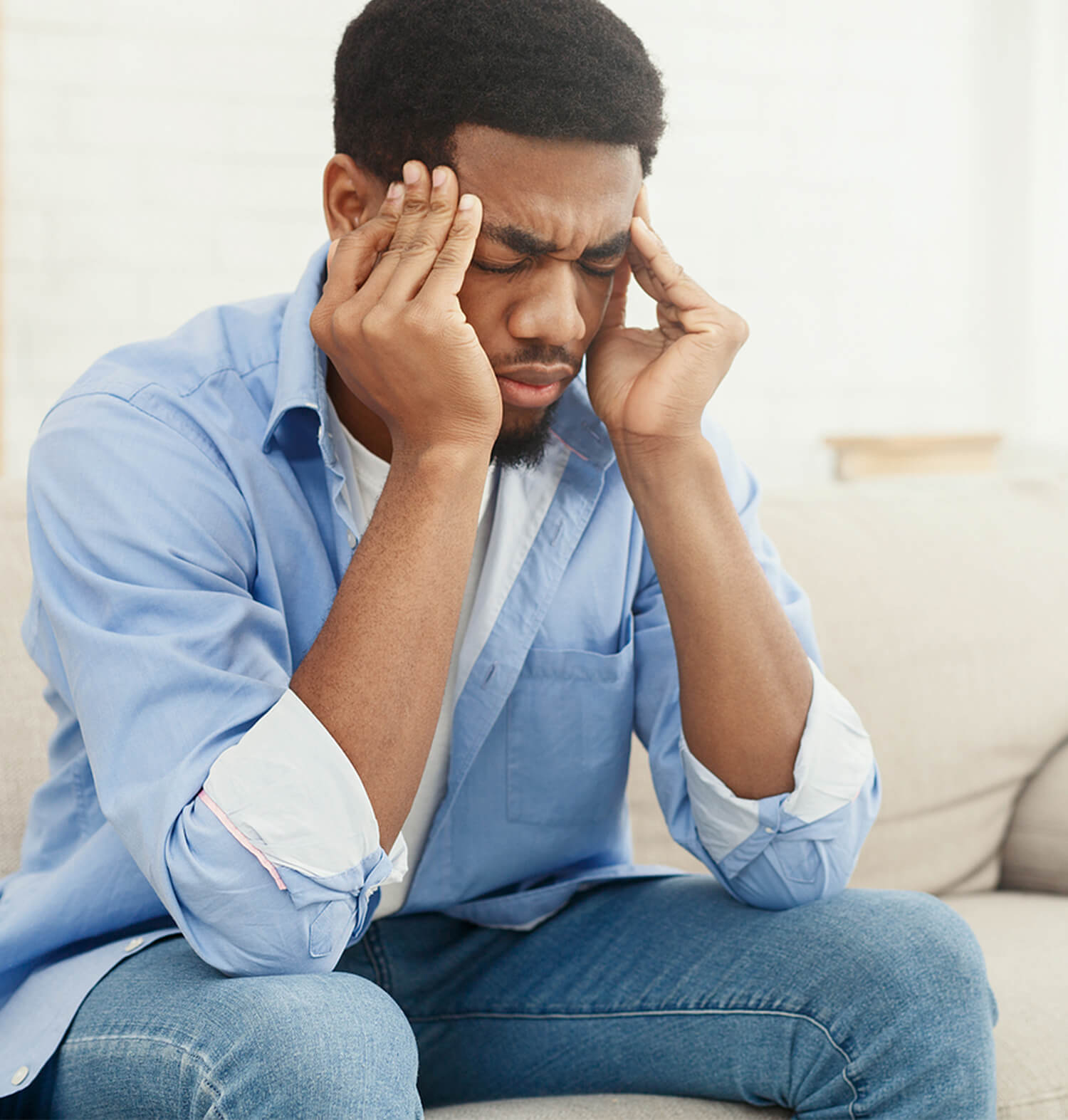 Black man rubbing temples while sitting in distress. Symptoms of anxiety don't have to overtake your brain space. Start moving forward and coping with an anxiety therapist. In anxiety treatment in Torrance, CA and surrounding areas we can help with GAD, performance, social anxiety, and separation anxiety. Get in touch!