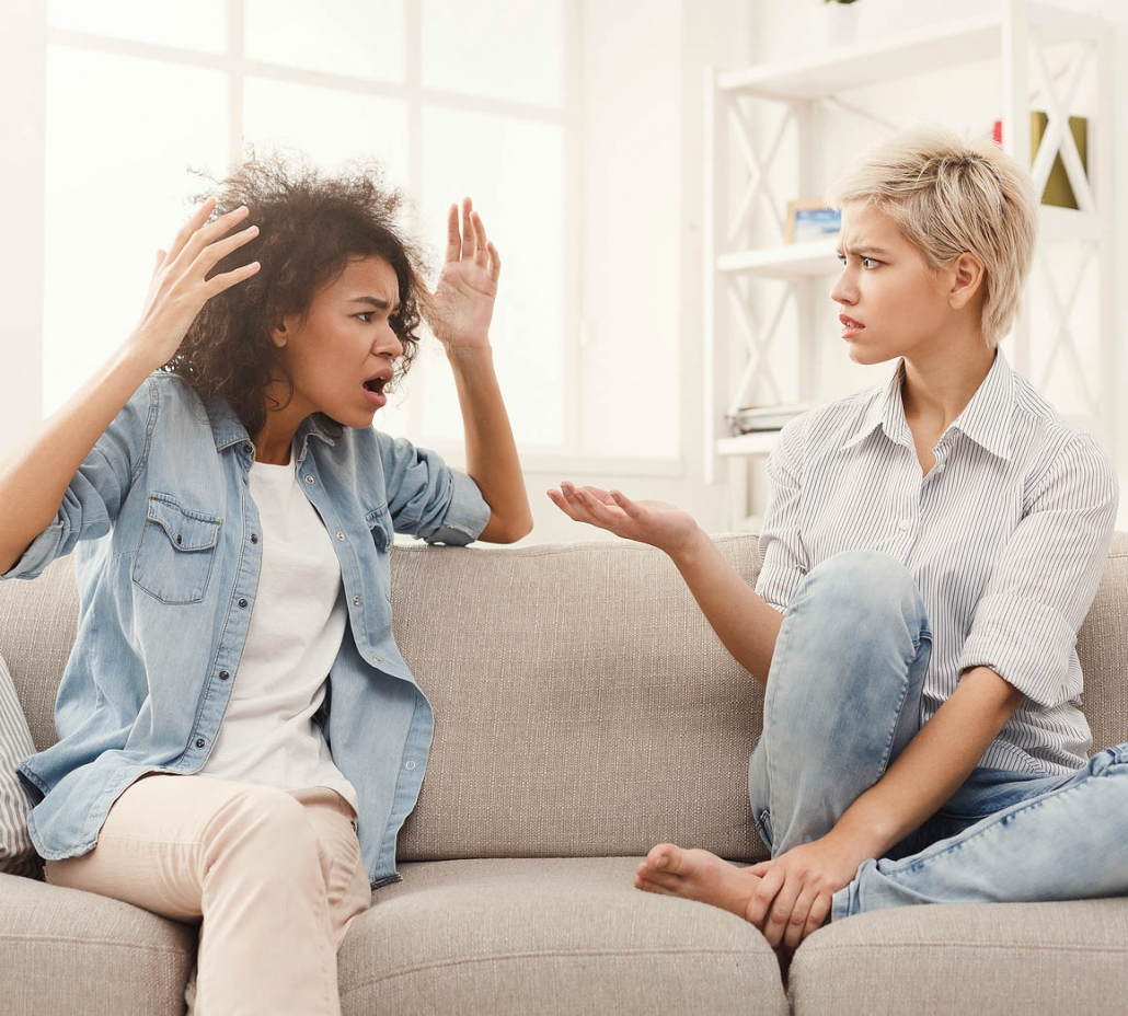 Mixed female couple sitting on couch in argument. Dealing with emotional distress in a relationship isn't help. Often you may want couples therapy or marriage counseling, but the other partner won't agree. Get support in relationship therapy in Torrance, CA and surrounding areas today!
