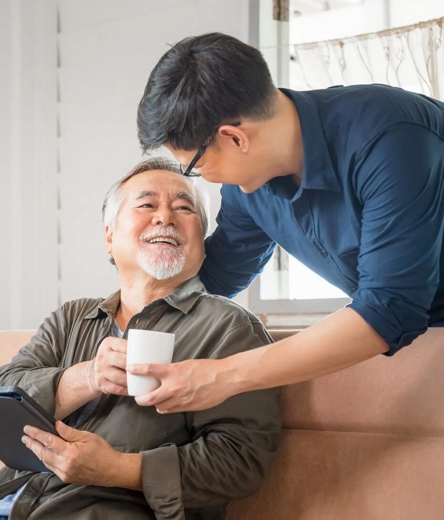 Son handing mug to smiling father. When communication comes first families thrive. Why not get support in therapy for siblings, mother-daughter therapy, mother-son therapy, therapy for blended families, or family therapy in Torrance, CA for everyone. Call now and get support from a family therapist soon!